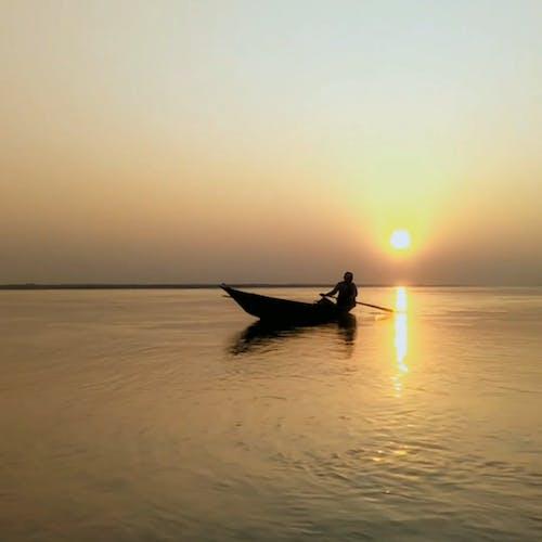 Silhouet Van Een Man Op Een Boot Bij Zonsondergang