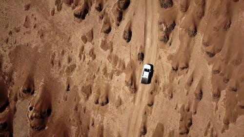 Vehicle Traveling Across The Desert Land