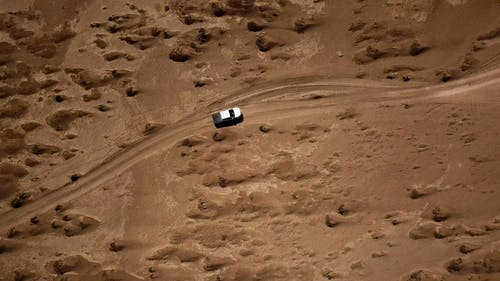 Vehicle Traveling In The Middle Of The Desert