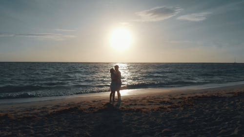 A Romantic Couple By The Seashore With View Of Sunset