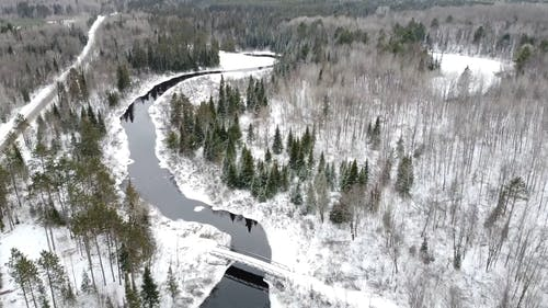 A Bridge Across The Forest River Covered In Snow