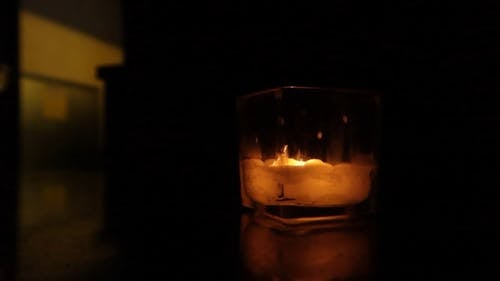 A Lighted Candle In A Glass
