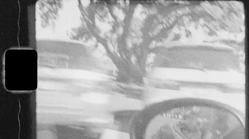Old Video Footage Of A Man Driving A Top Down Sports Car Around The City