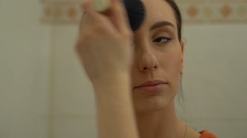 A Woman Applying Makeup Around Her Face