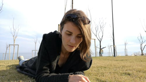 Woman In Black Coat Lying On The Ground While Reading In The Park