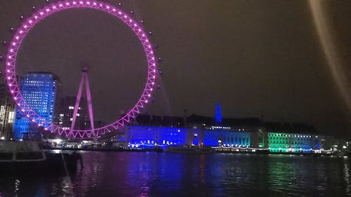 Colorful Lights Display Of London Eye And The Buildings Behind At Night