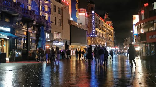 Groups Of People Talking and Standing In A Street In Leicester Square London