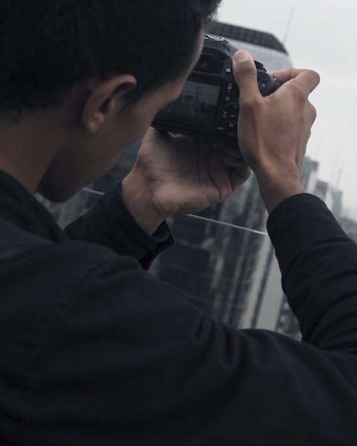 A Man Taking Photo On His Digital Camera