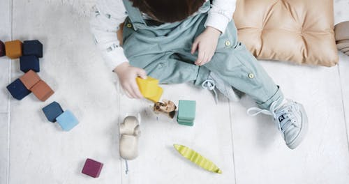 A Little Kid Is Playing With Color Coded Wooden Blocks