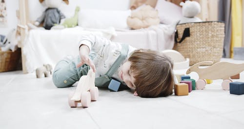 A Kid Playing With Wooden Toys In The Floor Of A Playroom