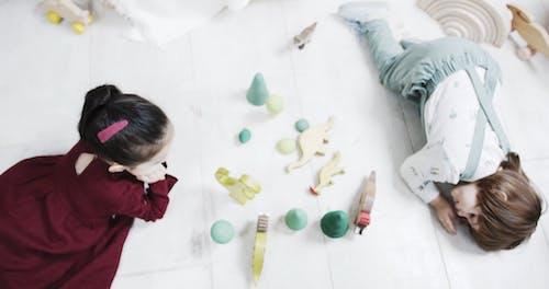 Kinderen Liggen Op De Vloer Tijdens Het Spelen Met Houten Dierenspeelgoed