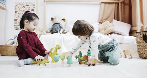 Two Little Kids Playing Wooden Toys On The Floor