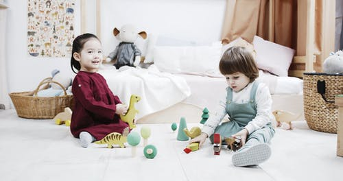 Two Kids Playing With Wooden Dinosaur Toys