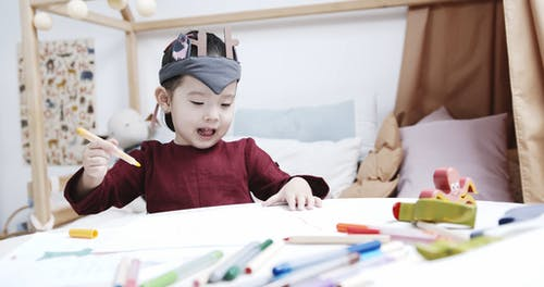 A Child Choosing Coloring Pens Of Different Color In Making A Drawing