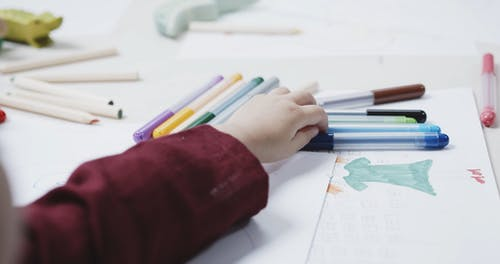 A Young Girl Using Coloring Pen To Draw On A White Paper