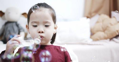 Дети дуют мыльные пузыри на игрушку для мыльных пузырей