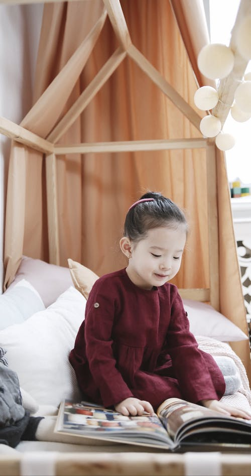 Little Girl Looking At Pictures In A Book While Sitting On A Bed