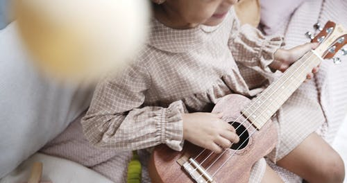 A Girl Happily Playing A Ukelele