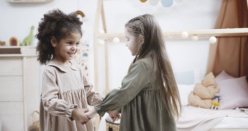 Two Little Girls Holding Hands Playing Round And Round