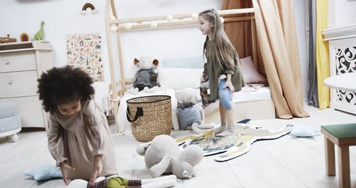 Two Young Girls Playing With Stuffed Toys In The Playroom