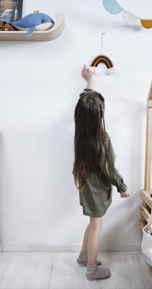 A Girl Swinging A Hanging Rainbow Stuffed Toy