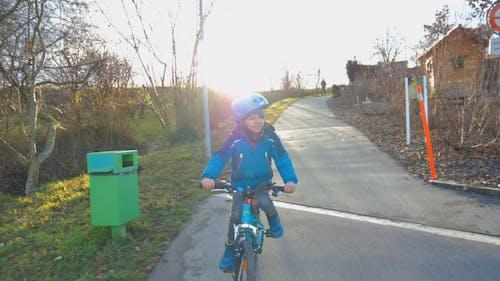 A Kid With Helmet Biking Along The Street