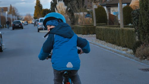 A Boy Riding A Small Bike In The Middle Of The Road