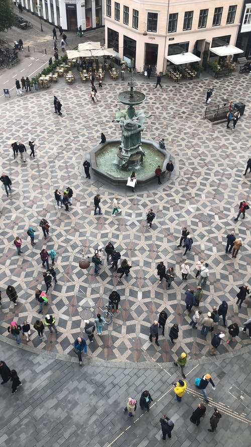 A Crowd Of People Gather In Plaza Where Water Fountain Is In Display