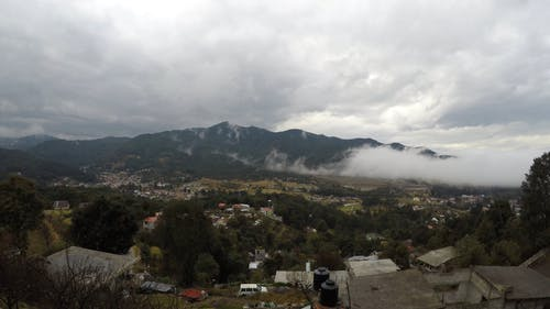 A Small Town Under Cloudy Sky In Timelapse Mode