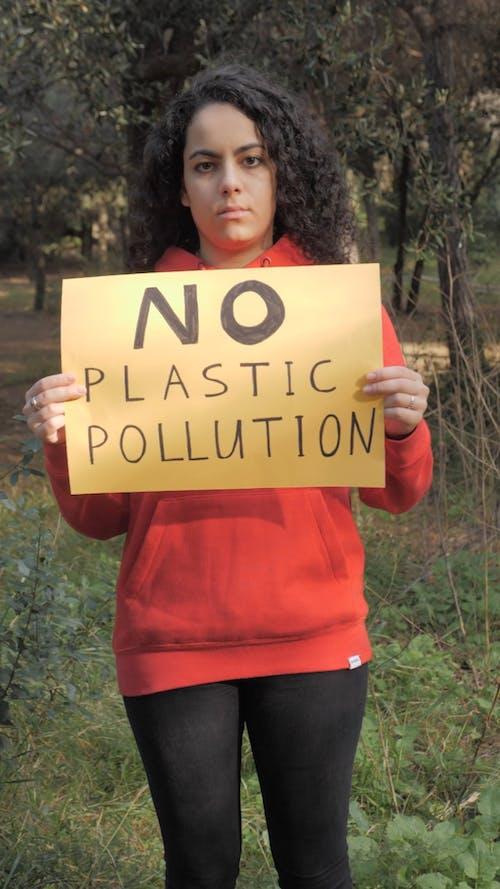 A Woman Holding AQ Slogan On Waste Disposal