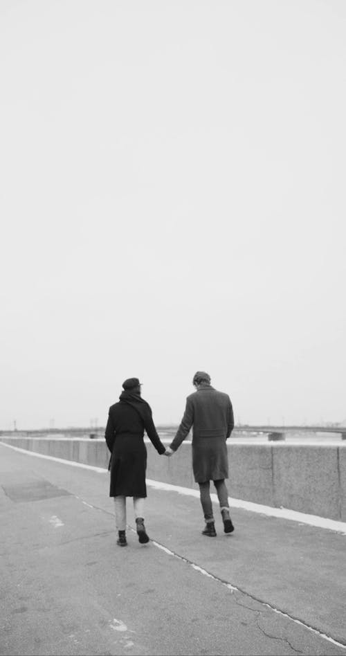 A Couple Walking Hand In Hand Along The Sidewalk By The Riverbank