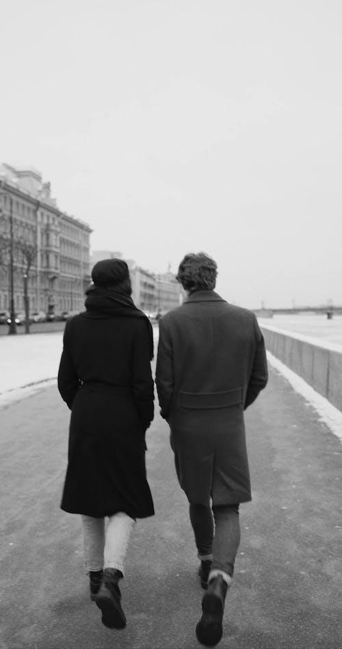A Couple Walking On A Sidewalk In Cold Winter