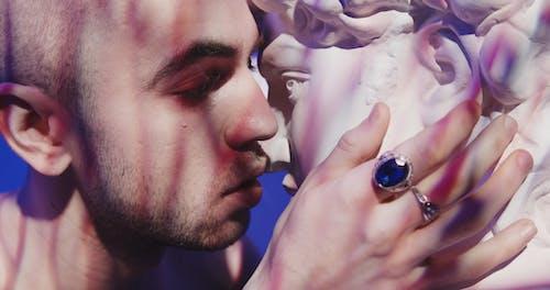 Man with Tears Kissing a Head Bust