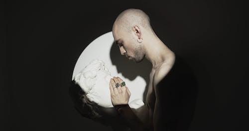 A Man Touching The Face Of A Head Bust Sculpture