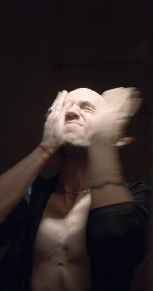 A Man Slapping And Grabbing His Face In Frustration