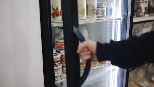 Adam Bir Bakkalın Buzdolabında Yiyecek Alıyor