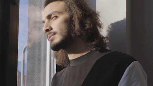 男子站在窗户与阳光透过他的脸