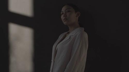 Woman In White Robe Blazer Posing Near A Wall