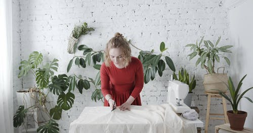 A Woman Cutting A  Piece From A Spread Of Fabric