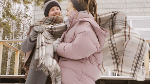 A Couple In Full Winter Clothes Hugging Outside In A Cold Weather