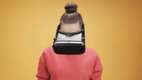 Woman In Pink Sweatshirt Menggunakan Virtual Reality