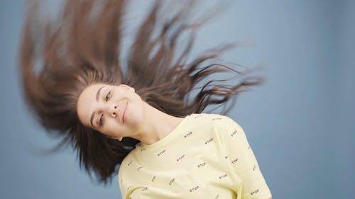 Женщина качает волосами движением головы