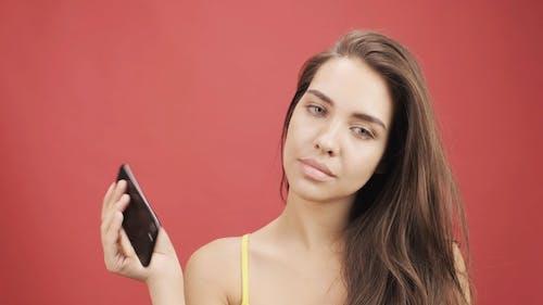 Seorang Wanita Dengan Gelisah Memutar Ponselnya Melalui Jari Jarinya