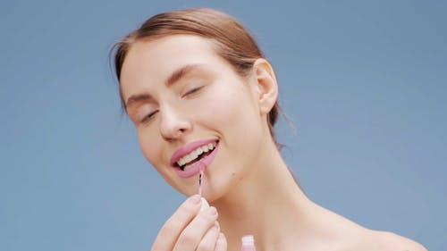 Woman Applying Pink Lipstick