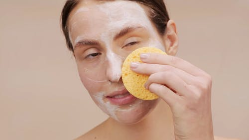 Woman Cleansing Her Face With Soap And Sponge
