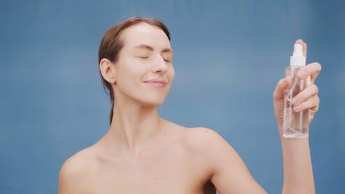 A Woman Moisturizing Her Face With Facial Spray