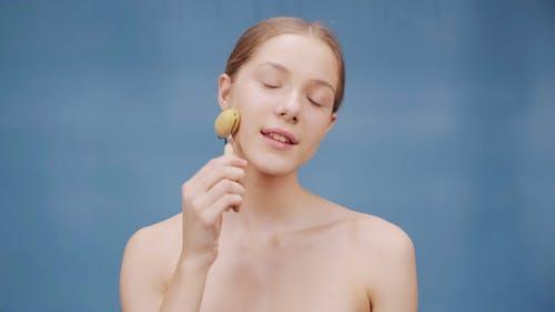 A Woman Using Jade Roller
