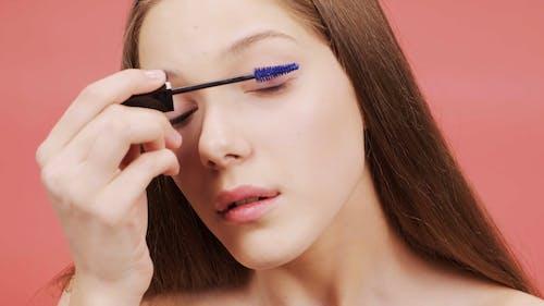 Woman Applying Purple Mascara