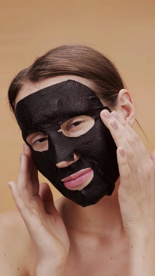 A Woman Removing A Charcoal Face Mask
