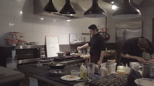 A Group Of Chefs Busy Working In The Restaurant Kitchen